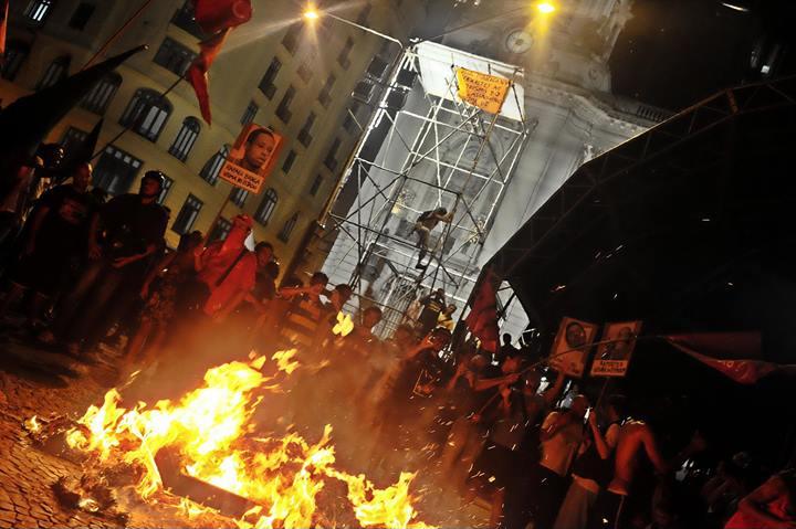 Indígenas da Aldeia Maracanã e manifestantes realizaram uma fogueira simbólica com jornais O Globo durante ato no Rio de Janeiro no dia 25/2. Ao fundo o cacique Zé Guajajara escala o palco montado para o carnaval carioca.